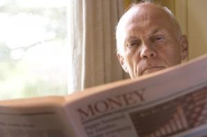 Senior man reading newspaper, close-up